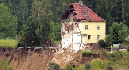 Landslide tips house into lake