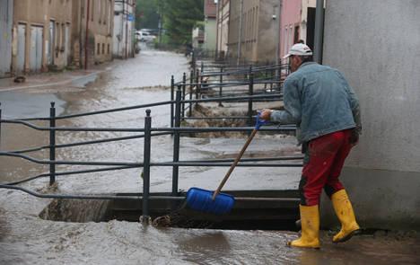 Floods kill cyclist and block roads