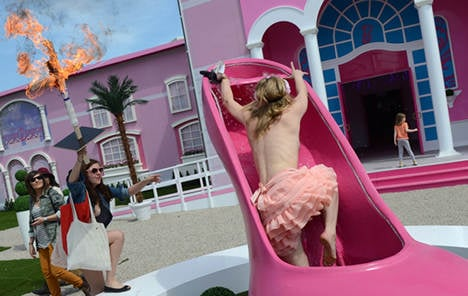 Giant Barbie doll house opens amid protests