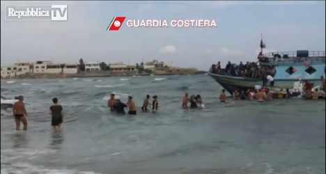 Beachgoers make human chain to save migrants