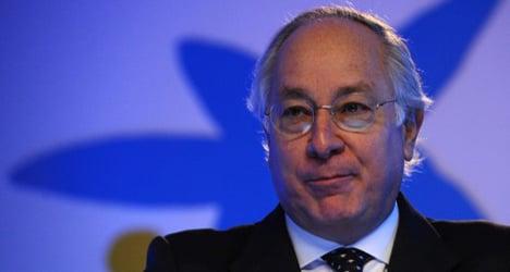 Spain's CaixaBank reports profits halved