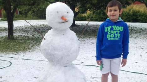 Swedish boy builds snowman in late June