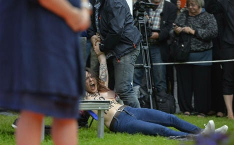 Reinfeldt's speech halted by topless protest