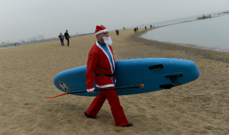 Surf's up: Dozens of Santas take to the waves in Barcelona
