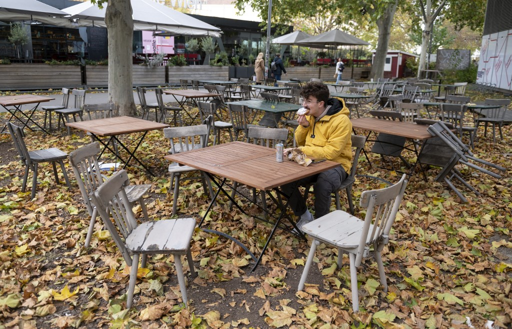 A man eats a sandwich in a deserted restaurant Schanigarten JOE KLAMAR AFP